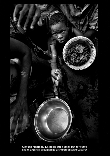 Clayson Menthor, 13, holds out a small pot for some beans and rice provided by a church outside Cabaret. (Photo Credit: Patrick Farrel, The Miami Herald, September 10, 2008 via the Pulitzer Prize website)