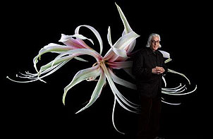 Jonathan Singer in front of his photograph of a Hippeastrum 'Toscana,' a new hybrid amaryllis. (Photo Credit: Howard Schatz via the artist's Website)